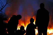 The silhouette of a family in front of their burning house.